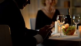Successful elderly man reading work email on smartphone during romantic dinner stock photography