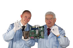 Successful IT - engineers. Presenting a motherboard, a fan and posing with the okay sign royalty free stock photography