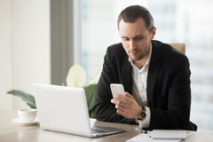 Successful entrepreneur using mobile app on phone. Successful businessman dials number on cellphone at desk with laptop. Attractive entrepreneur using mobile app Royalty Free Stock Images
