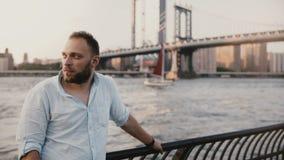 Successful European businessman stands at amazing sunset river near Manhattan Bridge New York, red yacht passes by 4K. Successful European businessman stands at stock video footage