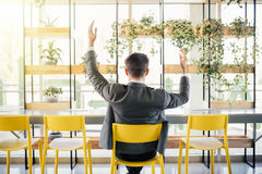 Successful excited business man happy smile hold fist gesture view from back, handsome young businessman with raised hands arms. Royalty Free Stock Images