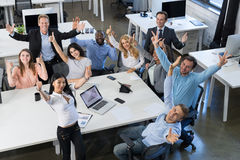 Successful Excited Mix Race Businesspeople Team Sitting At Table On Meeting, Holding Raised Hand Happy Smiling Business Royalty Free Stock Image