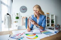 Successful fashion designer. attractive young happy casual trendy caucasian blonde fashion designer businesswoman in royalty free stock photography