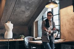 Successful fashion designer. Serious young woman in eyewear look. Ing away and keeping arms crossed while leaning on the desk in her workshop Stock Image