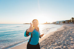 Successful female athlete doing positive thumbs up gesture and wearing earphones before running or exercising outdoor Stock Images
