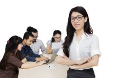 Successful female Chinese business leader. Young female Chinese business leader standing in front of her team in the office Royalty Free Stock Photos