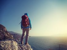 hiker stand on sunrise seaside mountain cliff edge Stock Photos