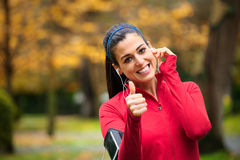 Successful female runner with earphones. Successful female athlete doing positive thumbs up gesture and wearing earphones before running or exercising outdoor in Royalty Free Stock Images