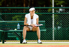 Successful female tennis player rests at the bench Royalty Free Stock Photos