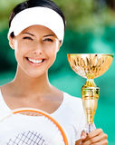Successful female tennis player won competition. Successful female tennis player won the cup at the sport competition. Victory Royalty Free Stock Photography