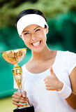 Successful female tennis player won the cup. Tennis player won the cup at the sport competition. Trophy Royalty Free Stock Images