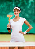 Successful female tennis player won the match. Tennis player won the cup at the sport contest. Award Stock Photo