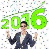Successful female worker with numbers 2016. Photo of cheerful female entrepreneur celebrate her success with numbers 2016 on the background Royalty Free Stock Image