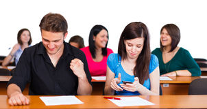 Successful Finals. Boy excited about successful finals, girl texting the results in classroom stock images