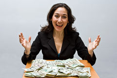 Successful finance. Happy business woman sitting at a table covered with stacks of money isolated on a white background stock image