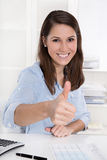 Successful first job: happy brunette woman in blue sitting at de Royalty Free Stock Images