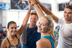 Successful fitness class. Happy fitness class giving high-five after completing exercise session. Group of sporty people giving high five and looking at camera Royalty Free Stock Image