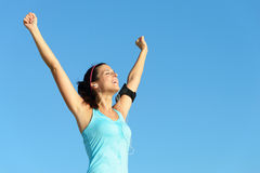 Successful fitness woman with earphones. Fitness and exercising success. Sweaty woman listening music through earphones raising arms to clear blue sky Stock Images