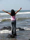 Successful Freedom. A teenage girl stretching out her arms at the sea depicting freedom & success Stock Photography