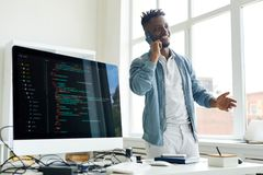 Successful freelance coder on phone. Cheerful successful young African-American freelance coder with beard gesturing while talking on phone in home office stock photo