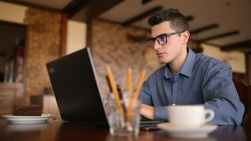 Handsome freelancer businessman in glasses diligently working on laptop in cafe. Man typing on keyboard and searches new. Successful freelancer sitting in cafe stock video footage