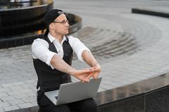 Successful freelancer working with laptop outdoors. Successful young freelancer working with laptop outdoor. He is wearing jacket and white shirt, with glasses Royalty Free Stock Image