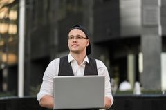 Successful freelancer working with laptop outdoors. Successful young freelancer working with laptop outdoors in front of office building Royalty Free Stock Photos