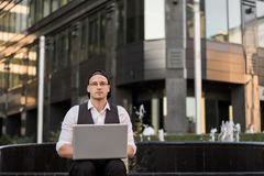 Successful freelancer working with laptop outdoors. Successful young freelancer working with laptop outdoor. He is wearing jacket and white shirt, with glasses Stock Images