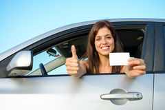 Successful girl in car with driving license. Female young car driver going thumbs up after passing the driving license test. Successful woman showing blank card Royalty Free Stock Image