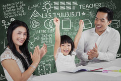 Successful girl get applause. Portrait of happy little girl raise hands after finish her homework and get applause Stock Image