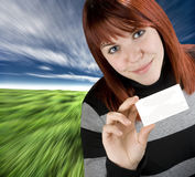 Successful girl holding a black business card. Smiling successful girl with red hair holding a blank empty business or greeting card. Studio shot royalty free stock images