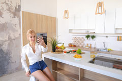 Successful girl and housewife calls on cell on video call and ch Royalty Free Stock Photo