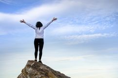 Successful girl open hand on top of mountain summit. Rock Royalty Free Stock Image