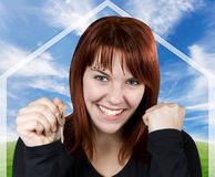 Successful girl smiling holding keys. Studio shot of a cute girl with red hair holding keys with a blue sky and green pasture background with a house symbol Stock Photo