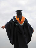 Successful Graduate. A female graduate raising arms in prayer for her success. Also to welcome her bright future.The sky is very bright  to celebrate her Stock Images