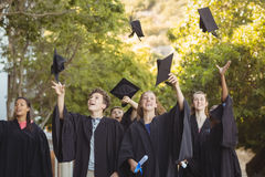 Successful graduate school kids throwing mortarboard in air in campus Royalty Free Stock Image
