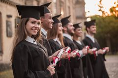 Happy young alumni stock images
