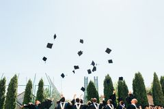 Successful graduates in academic dresses, toss up their hats, go royalty free stock photography