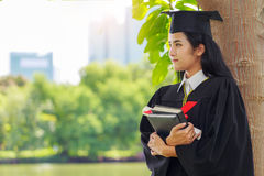 Successful graduating student wearing cap with book and gown hol. Ding diploma Royalty Free Stock Images