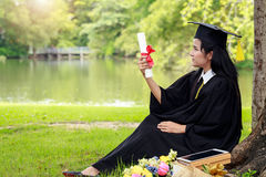 Successful graduating student wearing cap with book and gown hol. Ding diploma Stock Image