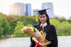 Successful graduating student wearing cap and gown holding diplo Royalty Free Stock Image