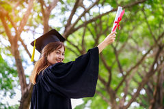 Successful graduating student wearing cap and gown holding diplo Royalty Free Stock Photography