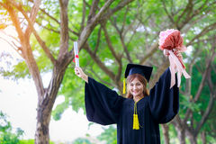 Successful graduating student wearing cap and gown holding diplo Stock Photos