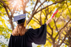 Successful graduating student wearing cap and gown holding diplo Royalty Free Stock Photos