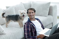 Successful guy and his pet in a cozy living room. Royalty Free Stock Photography