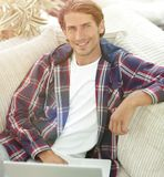 Successful guy working on laptop and looking at camera. view fro. Close-up. successful guy working on laptop and looking at camera. view from above. photo with stock image