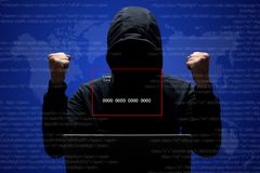 Successful hacker in black hoodie, being faceless, clenches fists, has success on stealing credit card, poses against digital inte stock photography
