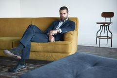 Successful young businessman is sitting on office sofa and looking at camera. Successful and handsome business man is sitting on office sofa and looking at royalty free stock image