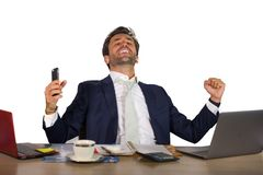 Successful handsome businessman in suit working at office computer desk celebrating financial success winning money smiling cheerf stock photo