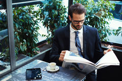 Successful handsome guy reading newspaper and waiting his girlfriend. Portrait of a young handsome businessman reading a newspaper at his breakfast in coffee stock image